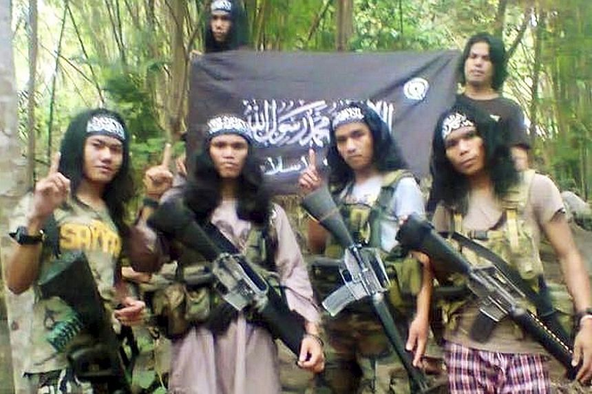 Hajar Abdul Mubin (extreme left) - otherwise known as Abu Asrie - in an undated photo taken in the southern Philippines. Hajar, a Filipino, was arrested along with one other Filipino and six Malaysians from the Borneo state of Sabah in a raid last We