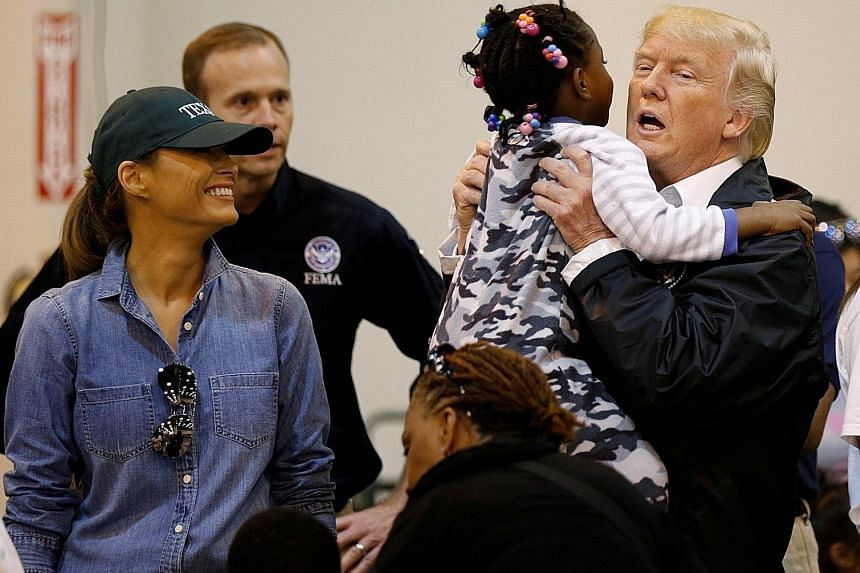 President Donald Trump holding a little girl as he and First Lady Melania Trump visit Hurricane Harvey flood survivors at a Houston relief centre on Saturday.