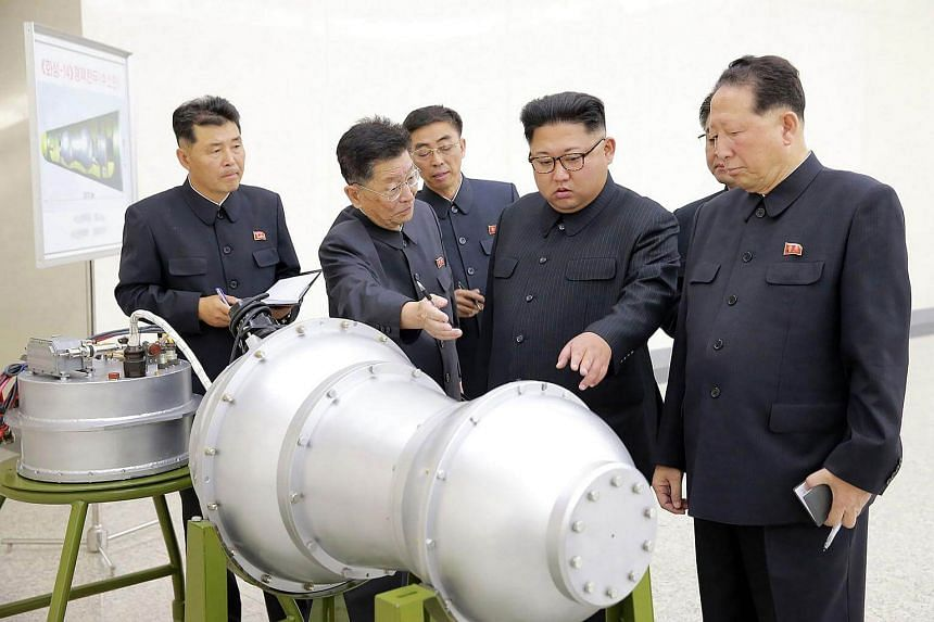 North Korean leader Kim Jong Un (centre) looking at a metal casing with two bulges at an undisclosed location on Sept 3, 2017.