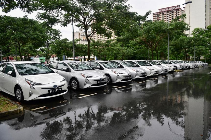 A fleet of private-hire Toyota Prius hybrid cars lined up in a carpark in Holland Village waiting for hirers.