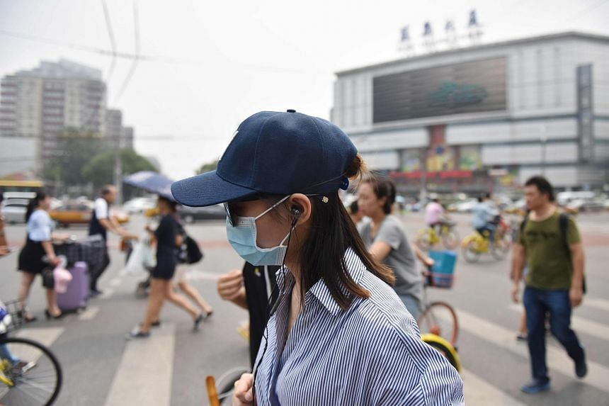 People cross an intersection on a hazy day in Beijing on July 20, 2017.
