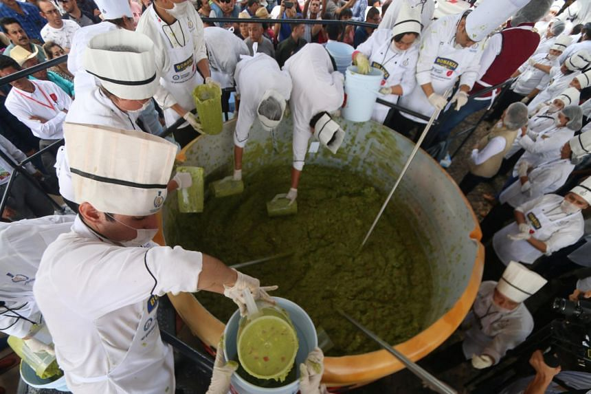 Volunteers from a culinary school mix mashed avocados as they attempt to set a new Guinness World Record for the largest serving of guacamole in Concepcion de Buenos Aires, on Sept 3, 2017.