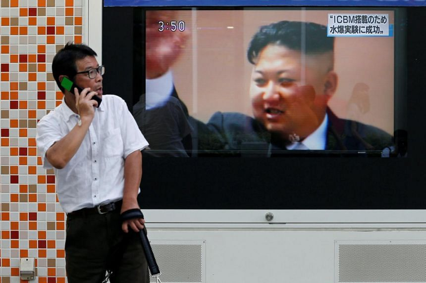 A man walks past a street monitor showing North Korea's leader Kim Jong-Un in a news report about North Korea's nuclear test, in Tokyo, Japan, on Sept 3, 2017.