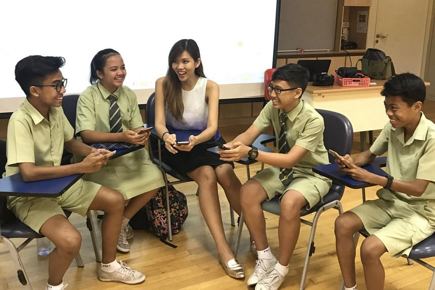 Miss Mavis Ho, 26, a teacher at Pasir Ris Secondary School, facilitating a group discussion with her students, with the use of The Straits Times NewsEd app.