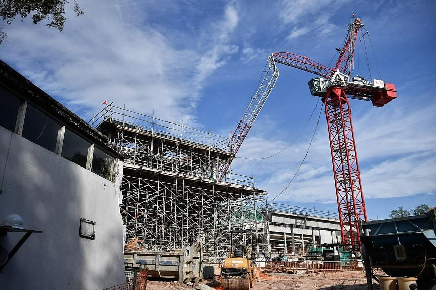 The crane's load-bearing arm is bent to a point where it is resting on the site where a two-storey bungalow is being built.