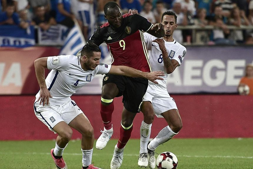Belgium striker Romelu Lukaku trying to get past Greece's Zeca (right) and Konstantinos Manolas during their World Cup qualifier on Sunday. Belgium won 2-1 and became the first nation from Europe and sixth team to qualify for the tournament in Russia