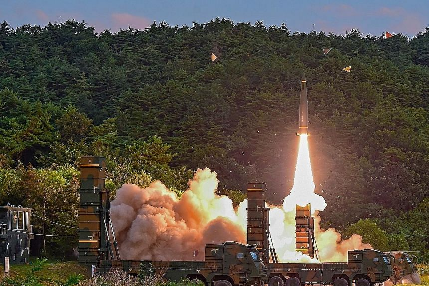 Left: A Hyunmoo-2 missile being launched at an undisclosed location on the east coast of South Korea yesterday during a live-firing exercise, after North Korea's sixth nuclear test a day earlier. A sign denoting a bomb shelter at a subway station in