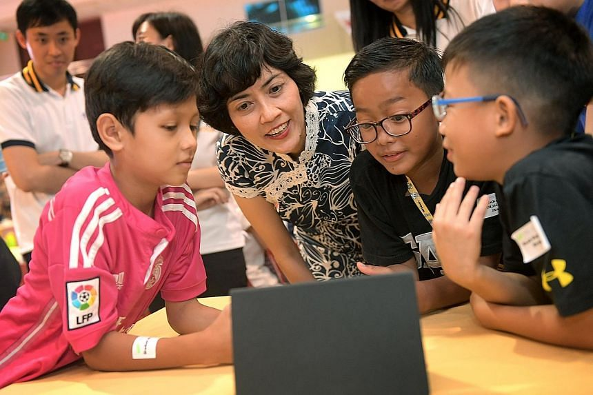 Kidstarter programme participants (from left) Dahri Daud, 11, Muhamad Matin Manaf, 10, and Noah Ong Tian Hong, eight, showing Tanjong Pagar GRC MP Joan Pereira the game they designed during their coding workshop, at Henderson Community Club yesterday