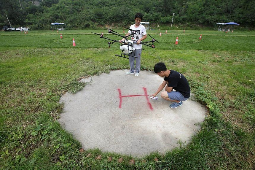 An instructor sets up landing sign as a trainee prepares to learn to fly an aerosol drone at LTFY drone training school on the outskirts of Beijing, China, on Aug 2, 2017.
