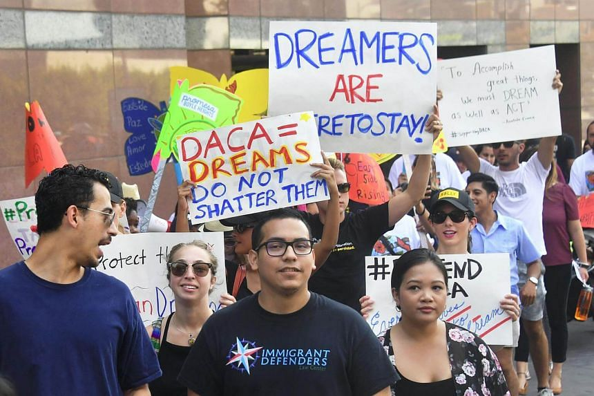 Young immigrants and supporters walk holding signs during a rally in support of Deferred Action for Childhood Arrivals (DACA) in Los Angeles on Sept 1, 2017.