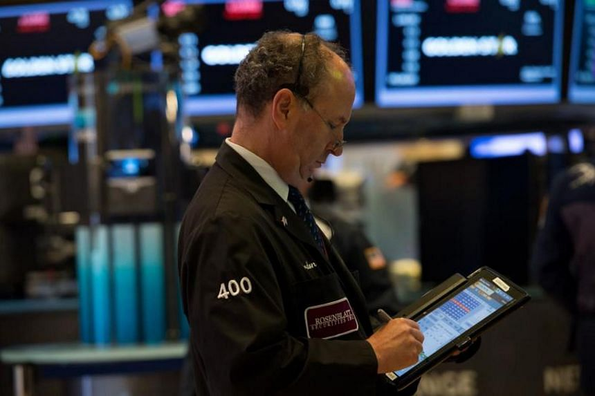 This file photo taken on Aug 8, 2017 shows a trader working on the floor at the closing bell of the Dow Industrial Average at the New York Stock Exchange in New York.