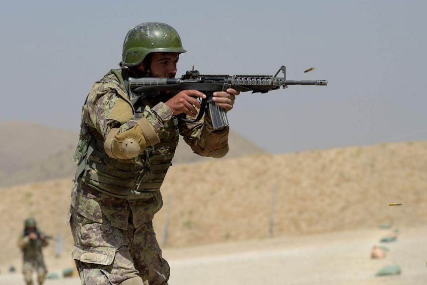 An Afghan commando opens fire during live firing exercises at Camp Morehead on the outskirts of Kabul on Aug 10, 2017.