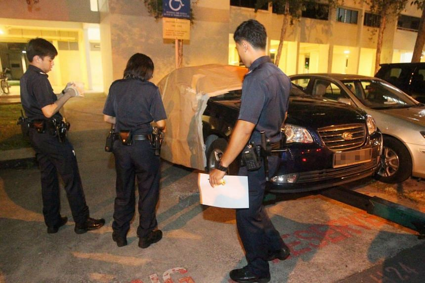 Police officers at the crime scene where money- changing business manager Ali Yousof Saiboo was robbed of more than $600,000 in cash at the carpark at Block 110 Aljunied Crescent on Nov 5, 2014.