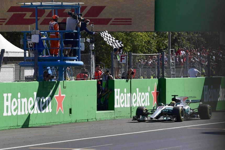 Mercedes' British driver Lewis Hamilton crosses the finish line to win the Italian Formula One Grand Prix at the Autodromo Nazionale circuit in Monza on Sep 3, 2017.