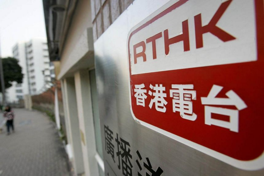 A woman walks past the television house of Radio Television Hong Kong in Hong Kong.