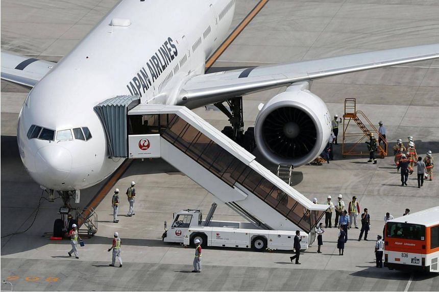 A Japan Airlines plane bound for New York that returned to Tokyo's Haneda airport for an emergency landing due to engine trouble, is seen at the airport in Tokyo, Japan on Sep 5, 2017.