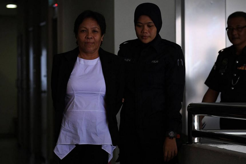 Australian national Maria Elvira Pinto Exposto (left) is escorted by a Malaysian policewoman as she arrives for her trial at the Shah Alam court in Selangor on Sept 5, 2017.
