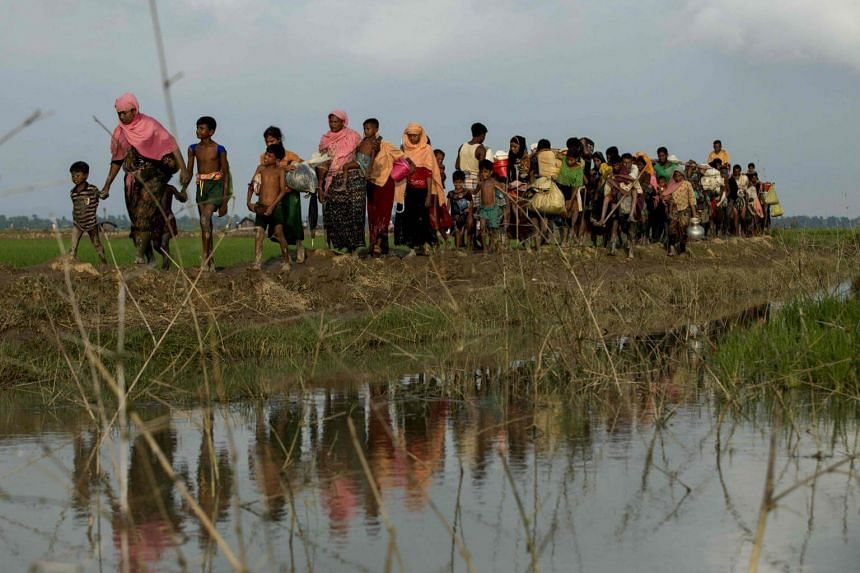 Displaced Rohingya refugees from Rakhine state in Myanmar carry their belongings as they flee violence, near Ukhia, near the border between Bangladesh and Myanmar on Sep 4, 2017.