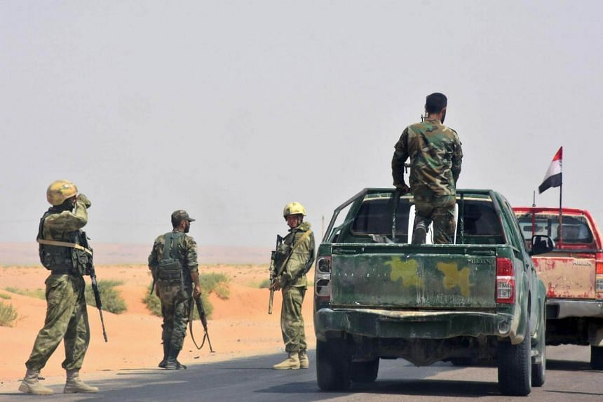 Syrian pro-government forces gather on a road in Bir Qabaqib, more than 40 kilometres west of Deir Ezzor, after taking control of the area on their way to Kobajjep in the ongoing battle against Islamic State group jihadists on Sept 4, 2017.