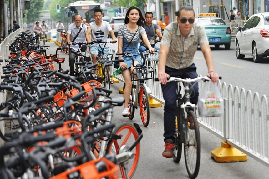 People ride past shared bikes at a bike lane in Wuhan, Hubei province, China, on June 26, 2017.