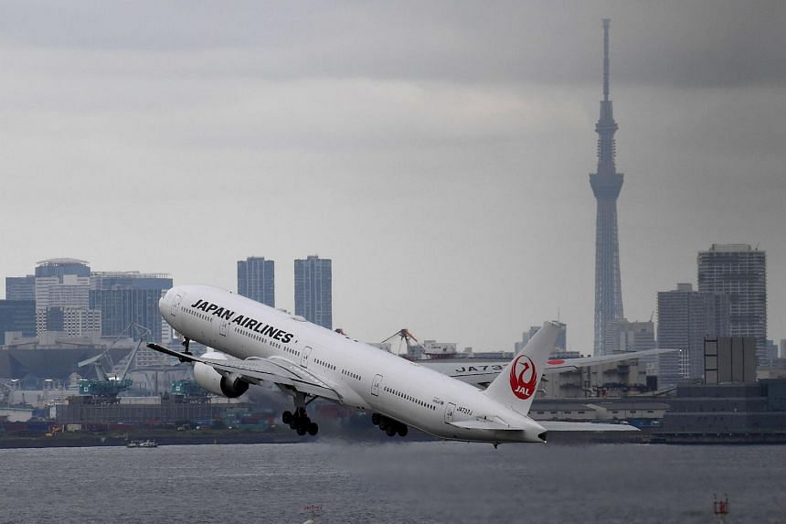 The landmark Tokyo Skytree tower is seen with the city skyline as a Japan Airlines (JAL) Boeing 777 takes off at Haneda international airport in Tokyo on Aug 2, 2017.