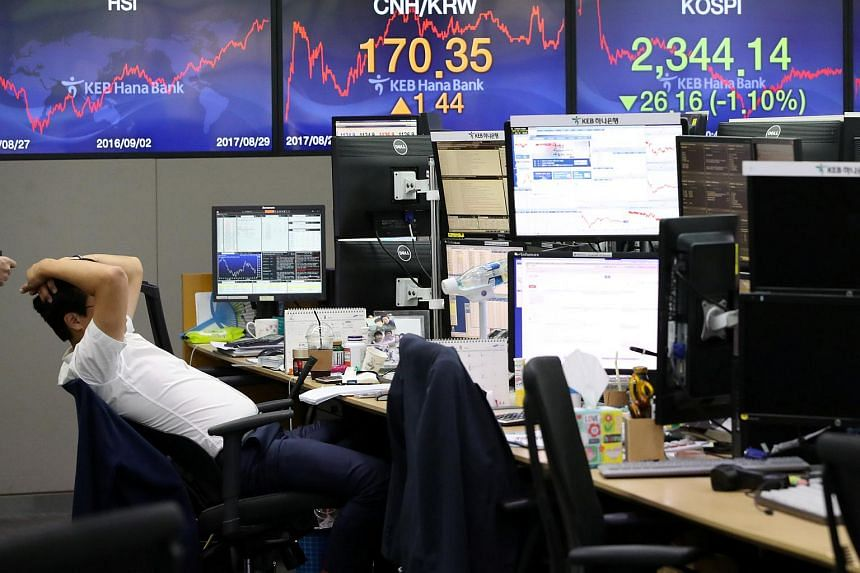 A currency dealer in front of electronic boards showing the Korea Composite Stock Price Index at a dealing room of a bank in Seoul.