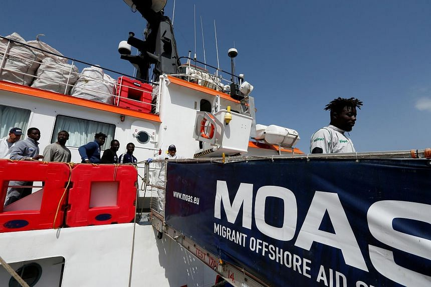 Migrants disembark from the Malta-based NGO Migrant Offshore Aid Station (MOAS) ship Phoenix on the island of Sicily, Italy, on May 6, 2017.