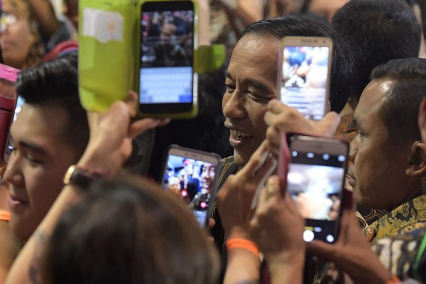 People take photos of President Joko Widodo as he makes his way to the stage.