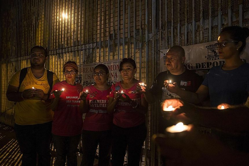 Activists at the wall between Mexico and the US during a protest on Monday against the possibility of deportation of Dreamers.