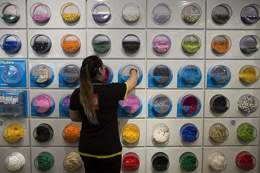 An employee in the Lego flagship store at Forum des Halles shopping centre, in central Paris. The Danish toymaker, known for its iconic coloured plastic bricks, said yesterday it would cut 1,400 jobs around the world before the end of the year. The c