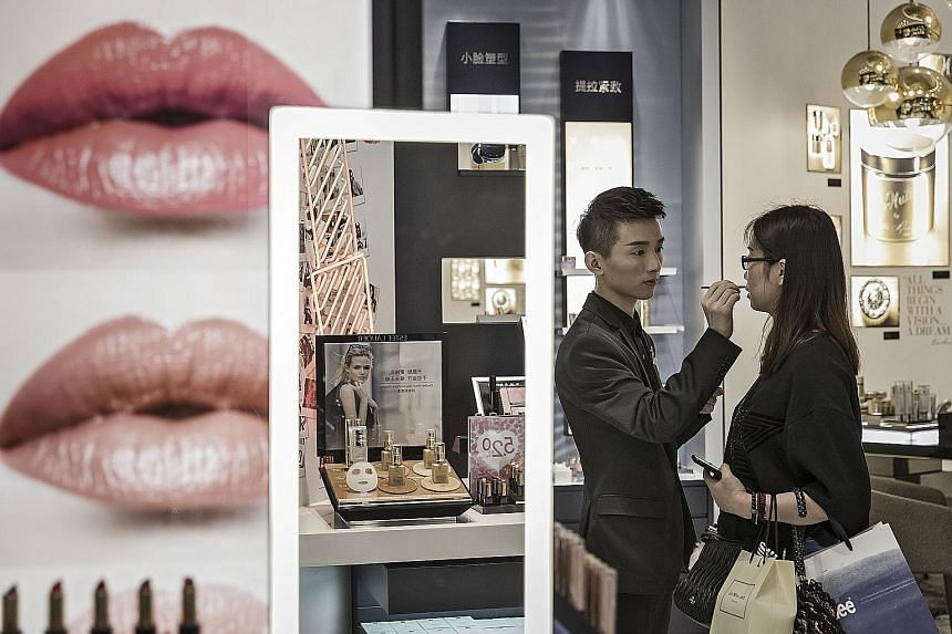 A sales assistant helps a customer try a lip colour in a mall in Shanghai. The Caixin/Markit services purchasing managers' index rose to 52.7 last month - the highest reading in three months - from 51.5 in July.