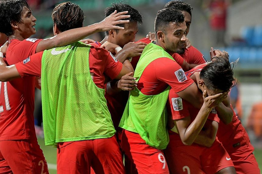 The Lions celebrating the game's opening goal by Shakir Hamzah (right) against Turkmenistan in the Asian Cup qualifier at Jalan Besar Stadium yesterday. The 1-1 draw means that Singapore remain at the bottom of Group E with two points after two draws