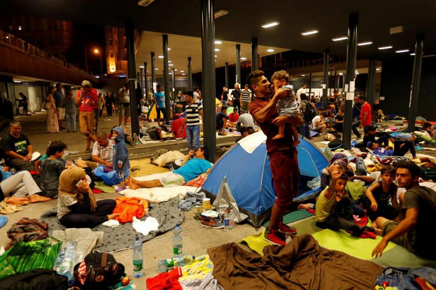 This file picture shows asylum seekers waiting outside a train station in Budapest, Hungary.
