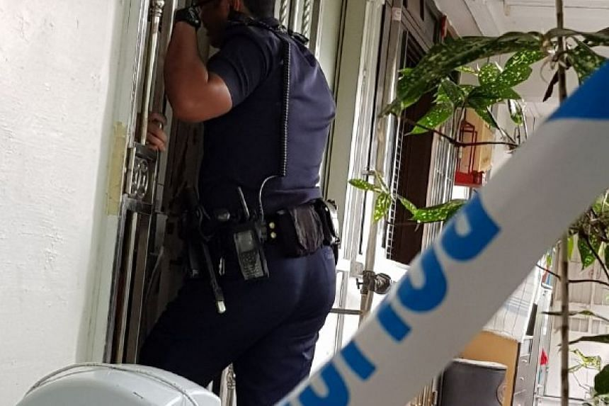 A policeman looks into the flat at 1 Marsiling Drive.