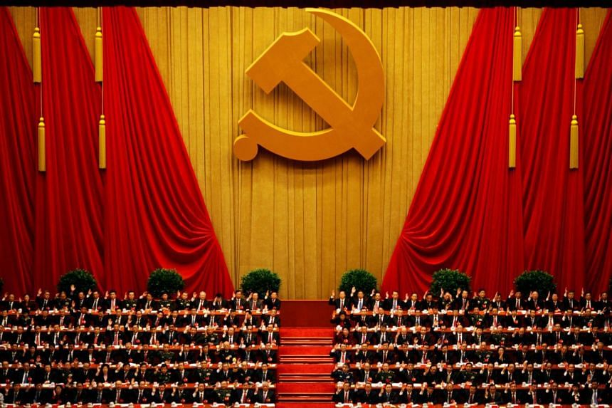 Delegates raising their hands as they take a vote at the closing session of the 18th National Congress of the Communist Party of China at the Great Hall of the People in Beijing on Nov 14, 2012.