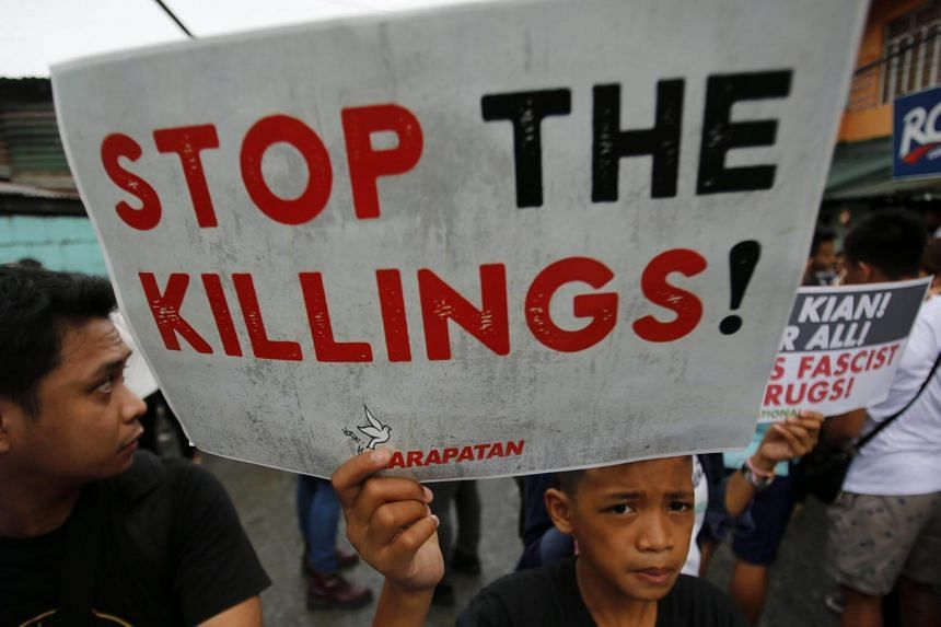 A Filipino symphatiser holds a placard while joining the funeral for student Kian Delos Santos, on a street in Manila, Philippines on Aug 26, 2017.