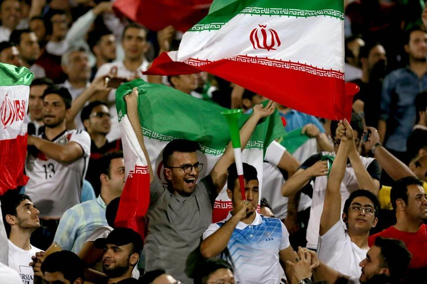 Supporters of Iran cheer for their team during the Fifa World Cup 2018 qualification match between Syria and Iran at the Azadi Stadium in Teheran on Sept 5, 2017.