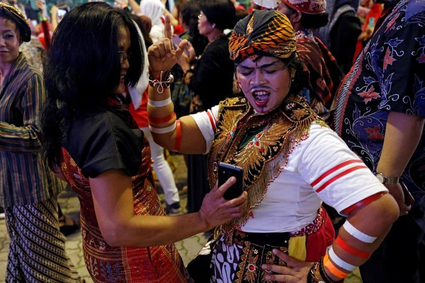 Domestic helper Triningsih, 43, of Semarang dances in her traditional costume with a crowd made up largely of domestic helpers, as they wait for the arrival of Indonesia's President Joko Widodo at the Indonesian embassy in Singapore on Sept 6, 2017.