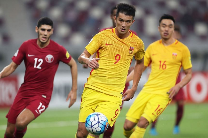 China's Xiao Zhi (centre) controls the ball during the match against Qatar.