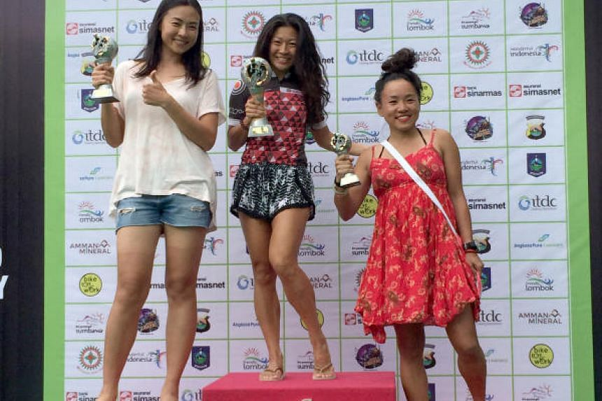 Shirley Teo (centre) lifting her GFNY Indonesia trophy in celebration after winning the overall female title.
