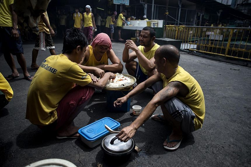 Inmates eating their lunch inside the Quezon City Jail in Manila, on July 11, 2017.