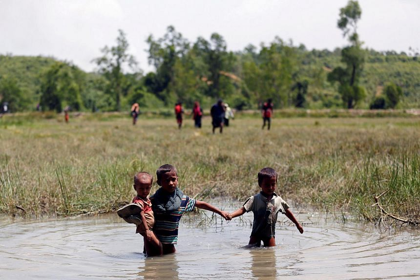 Rohingya children make their way through water as they try to come to the Bangladesh side from No Man's Land after a gunshot was being heard on the Myanmar side, in Cox's Bazar, Bangladesh on Aug 28, 2017