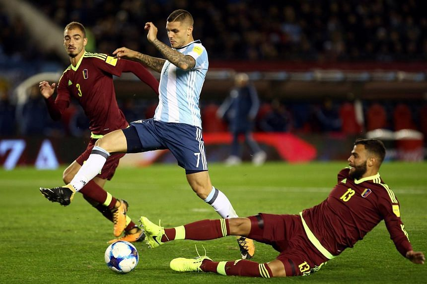 Argentina's Mauro Icardi is challenged by Venezuela's Mikel Villanueva and Jhon Chancellor at the Monumental stadium, Buenos Aires, Argentina on Sept 5, 2017.