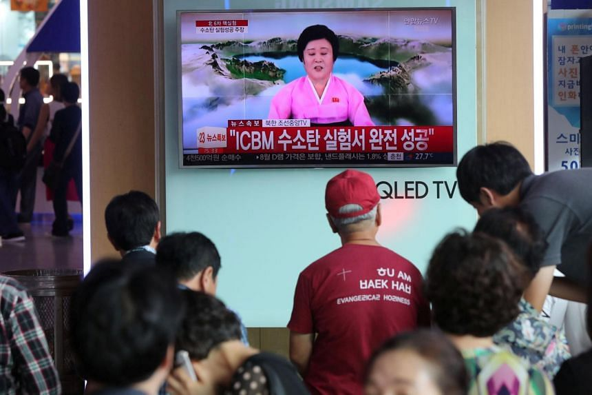 People watch a TV news report about North Korea's hydrogen bomb test at a railway station in Seoul, South Korea on Sept 3, 2017.