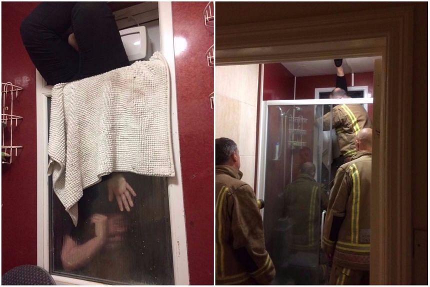 Firefighters rescuing the woman, who was trapped upside-down in a window while trying to retrieve her own poo.