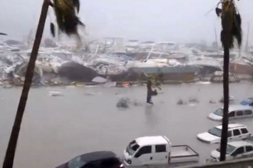 Half-submerged vehicles, boats and debris in the flooded harbour as Hurricane Irma hits the French island territory of Saint Martin.