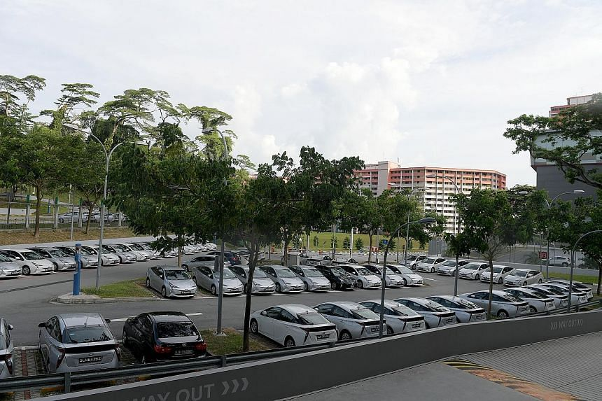 """Private-hire cars at Singapore General Hospital. On the lower COE price for smaller cars, Prime chairman Neo Nam Heng said private-hire giants """"have cooled down"""" in growing their fleets since new regulations started in July."""