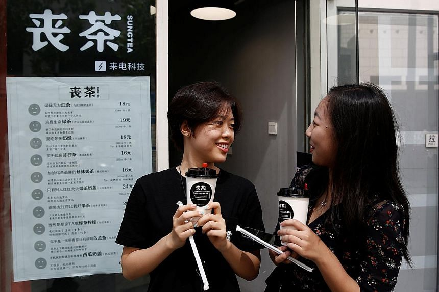 """Customers with cups of tea named in the fashion of the """"sang"""" subculture at the Sung Tea shop in Beijing last month. While the drink names are tongue-in-cheek - such as """"achieved-absolutely-nothing black tea"""" and """"my-ex's-life-is-better-than-mine fru"""