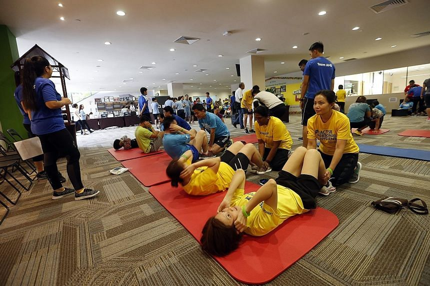 Staff of Khoo Teck Puat Hospital (KTPH) and Yishun Community Hospital doing sit-ups yesterday during an annual fitness challenge, which is held over three weeks. The more than 4,000 staff are encouraged to take part in the challenge, which also inclu