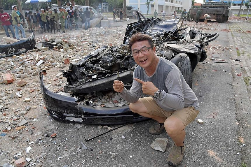 A car being crushed by a tank in Dover Road. Jack Neo (left) spent hours preparing for the set-up because there is enough time and money to do the stunt only once.